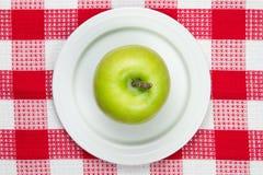 Pano de tabela quadriculado com placa e knif verde da maçã e da casca Imagem de Stock Royalty Free