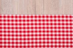Pano quadriculado vermelho e branco na madeira Fotos de Stock Royalty Free