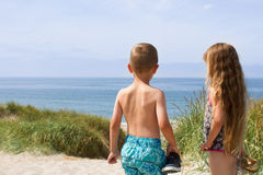 Panonamic view of North Sea beach. A young boy and a young girl with beautiful long hair is overlooking the shores of the Atlantic ocean. Boy is wearing Stock Photos