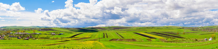 Panoramic view of farmland and sky. Panoramic view of  farm land with two villages on the side on a blue spring sunny day with a vibrant colorful look Royalty Free Stock Image