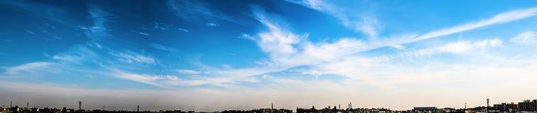 Panoram av moln i olika former med blåa himlar Arkivbild
