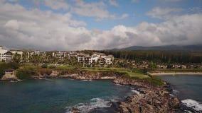 Panorama aéreo bonito da maioria de montagem cara kapalua do recurso e de ondas do estouro do oceano na ilha maui, Havaí filme
