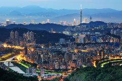 Panorama aéreo de comunidades suburbanas superpobladas en Taipei en la oscuridad, con la torre de Taipei 101 entre edificios aden Foto de archivo