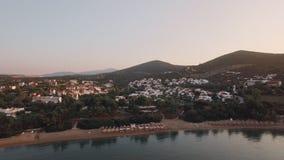 Panorama aéreo de las cabañas y de las colinas verdes, Grecia de la playa de Trikorfo almacen de video