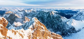 Panorama aéreo de montanhas rochosas nevado no por do sol Foto de Stock Royalty Free