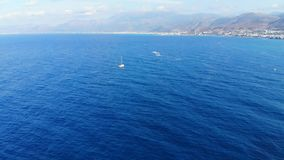 Panorama aéreo en el mar azul y pequeño el yate blanco que navegan lejos, Creta, Grecia almacen de metraje de vídeo
