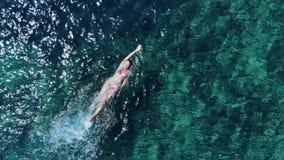 Panorama aéreo en la natación de la espalda de la mujer en el mar azul almacen de metraje de vídeo