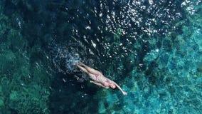 Panorama aéreo en swimmimg de la mujer en el mar azul almacen de metraje de vídeo
