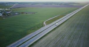 Panorama aérien de route avec le champ et le village Tir d'inclinaison de cuisson du bourdon 4K Industrie de réseau de transport  banque de vidéos
