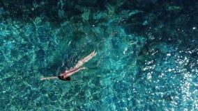Panorama aérien sur la femme de natation de détente en mer bleue banque de vidéos
