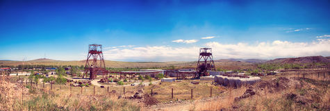 Panorama of an abandoned underground mine. Photo of an abandoned underground mine. Two mines and technological structures are visible against the background of a Royalty Free Stock Photography