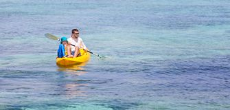 Family at vacation. Panorama of active family of two, father and son, enjoying kayaking together, tropical vacation concept, copy space on right Stock Photo
