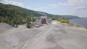 Panorama aereo di grande area della pianta del calcare in cava vicino al fiume, estraente archivi video