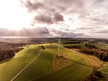Panorama aerial helicopter view over wind farm landscape in Germany with white generator turbines. A panorama aerial helicopter view over wind farm landscape in Royalty Free Stock Photo