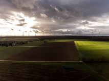 Panorama aerial helicopter view over wind farm landscape in Germany with white generator turbines. A panorama aerial helicopter view over wind farm landscape in Stock Images