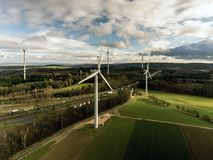Panorama aerial helicopter view over wind farm landscape in Germany with white generator turbines. A panorama aerial helicopter view over wind farm landscape in Stock Photos