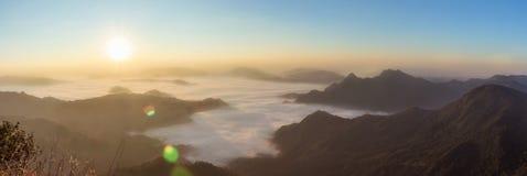 Panorama, alba di mattina con luce, chiarore nell'atmosfera nebbiosa circondata dalle montagne Fotografie Stock