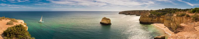 Panorama of the Algarve coastline in Portugal with a sailing boat moving towards the Marinha beach. There are cliffs, vegetation, a beach and rock stacks in stock photos