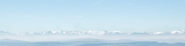 Panorama alpino Snowcapped e colline pedemontana nebbiose Immagine Stock Libera da Diritti