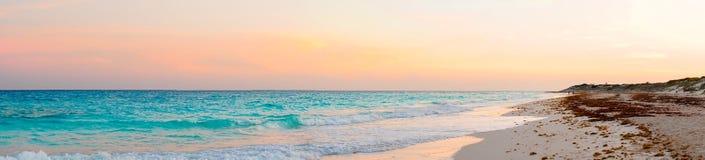 Panorama of amazing beautiful sunset on white sandy beach. Stunning beautiful sunset on an exotic caribbean beach Royalty Free Stock Photo
