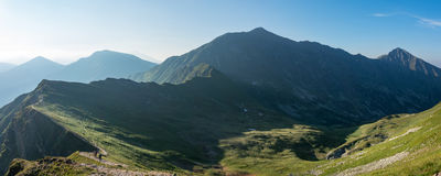 Panorama of amazing morning summer mountains with hikers Stock Photos