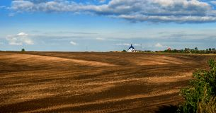 Panorama of brown arable land over amazing clouds. Panorama of arable land over amazing clouds Royalty Free Stock Photo