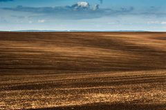 Panorama of arable land over clouds sky. Panorama of brown arable land over clouds sky Royalty Free Stock Image