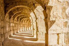 Panorama of Aspendos theatre arcade. Panorama of Aspendos theater arcade with morning light shooting through columns and creating geometric pattern of light and Stock Image