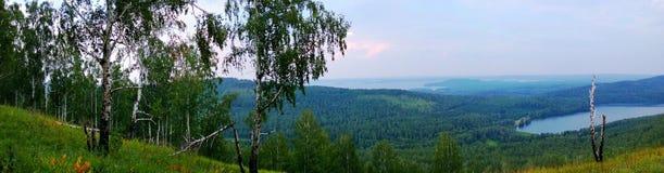 Panorama auf blauen Hügeln und See Stockfotos