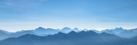 Panorama av bergen på soluppgång i en blå morgonogenomskinlighet royaltyfri fotografi