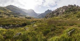Panorama av berglandskap med ängen som lokaliseras i ett River Valley Arkivbild