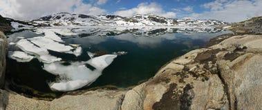 Panorama av bergsjön med reflexionen av bergen, Norge Royaltyfri Bild
