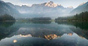 Panorama av den alpina sjön, soluppgång över den alpina sjön Laghi di Fusine Arkivfoto