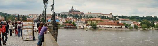 Panorama av den Charles Bridge och Vltava floden i Prague, med folk på bron och historiska byggnaderna på flodstranden Fotografering för Bildbyråer