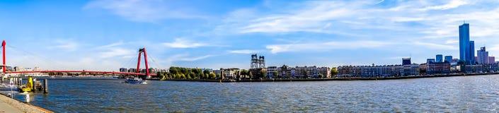 Panorama av den Nieuwe Maas floden med den röda kabeln blev Willems Bridge och de historiska husen på kusten av Noordereiland royaltyfria bilder