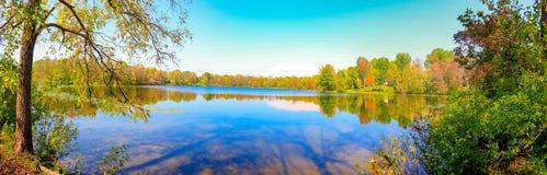Panorama av den sceniska rutten till och med nedgångskog med färgrik höstlövverk som reflekterar i sjön Lokaliserat i södra västr royaltyfria bilder