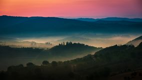 Panorama av den Tuscan vingården som täckas i dimma på gryningen nära Castellina i Chianti, Italien royaltyfri fotografi