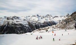 Panorama av det österrikiskt skidar semesterorten Ischgl med skidåkare Arkivfoto
