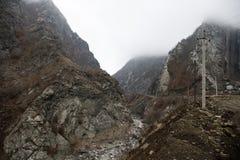 Panorama av det dimmiga vinterlandskapet i bergen med snö och vaggar, Azerbajdzjan, Lahic, stora Kaukasus Royaltyfri Foto
