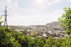 Panorama av en liten stad och hög-spänning ett elektriskt torn som levererar elektricitet till befolkningen arkivbilder