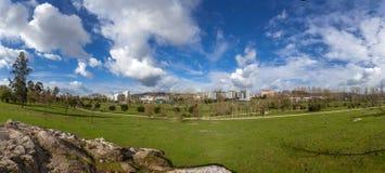 Panorama av ett stort tomt gräsmattafält för grönt gräs, med en sikt av staden i Parque da Devesa Urban parkerar fotografering för bildbyråer