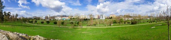 Panorama av ett stort tomt gräsmattafält för grönt gräs, med en sikt av staden i Parque da Devesa Urban parkerar royaltyfri foto