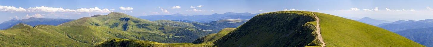 Panorama av gröna kullar i sommarberg med grusvägen för royaltyfria foton
