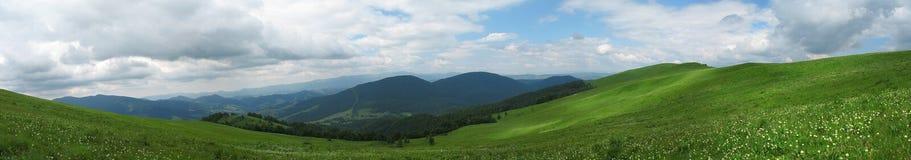 Panorama av härliga fält och berg för en vår Royaltyfria Bilder