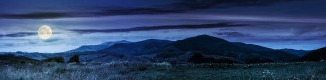 Panorama av lantliga fält i berg på natten Royaltyfria Bilder