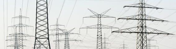 Panorama av många elektriska pyloner för energiförsörjning royaltyfri bild