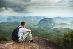 Panorama av passformen och den aktiva unga mannen som vilar efter vandring och tycker om sikt Tab Kak Hang Nak Hill naturslinga t royaltyfri foto