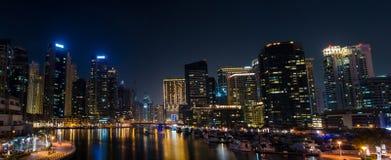 Panorama av upplysta skyskrapor med reflexion i vattennig Royaltyfri Fotografi