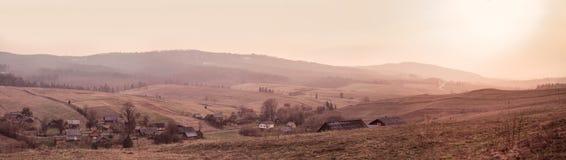 Panorama av vårsolnedgången i bergby royaltyfri foto