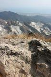 Panorama av viten marmorerar villebr?d av Carrara p? de Apuan fj?ll?ngarna De vita delarna av berget markerar omr?dena av stenen arkivfoton